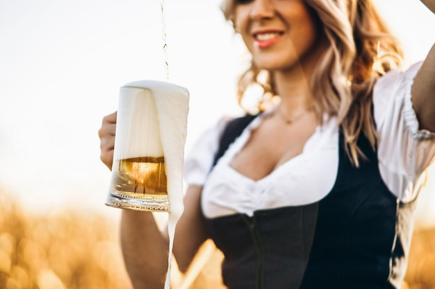 Крупным планом руки девушки в дирндль наливание полный стакан пива с огромной пеной на открытом воздухе
