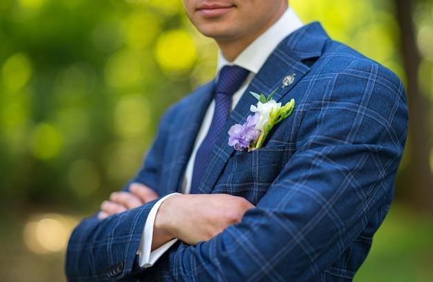 緑の庭を背景にブータニエールと青いスーツを着た新郎のクローズアップ。屋外の結婚式。