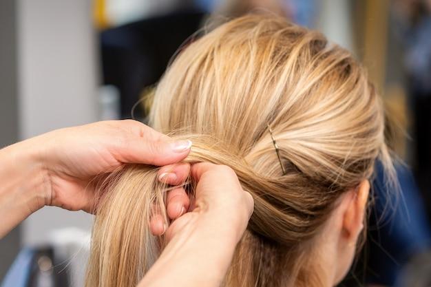 미용실에서 고객의 머리카락을 땋는 미용사의 손을 닫습니다.