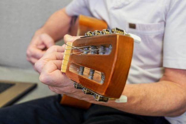 클래식 어쿠스틱 기타를 연주 백인 성인 남성의 손 클로즈업. 선택적 초점, 흐린 배경