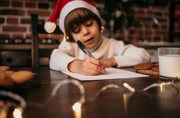 부엌에 앉아 새해 메시지를 쓰는 어린 소년의 손 클로즈업