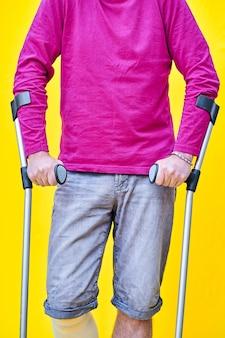 청바지에 남자의 목발과 붕대를 감은 다리가있는 보라색 티셔츠를 쥐고있는 손의 클로즈업.