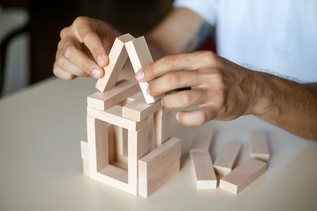 집의 모델을 만드는 남성 건축가의 손을 닫습니다. 남자 건축가는 사무실에서 일합니다.