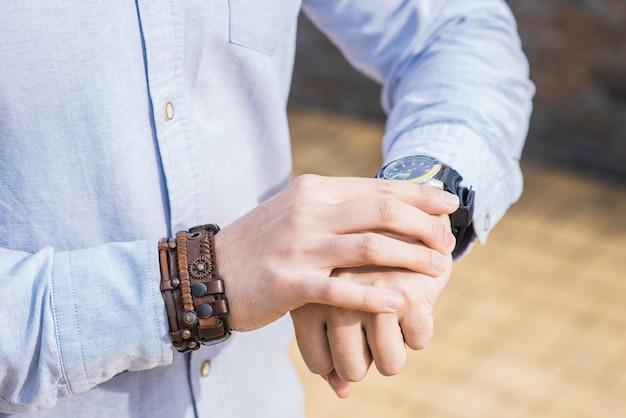 時計が置かれている男性実業家の手のクローズアップ
