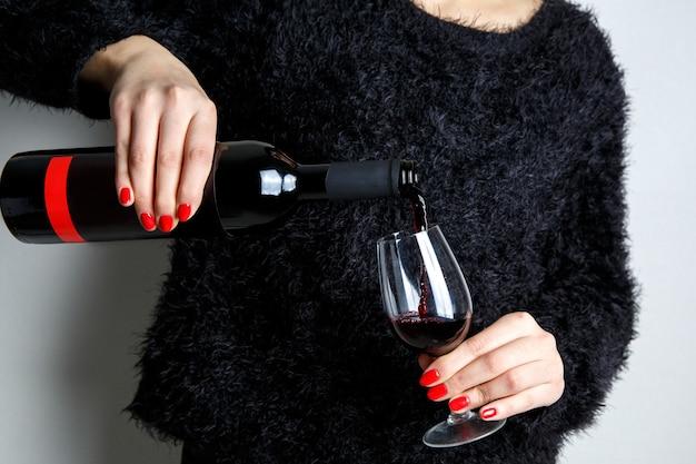 닫기 병에서 유리에 레드 와인을 붓는 젊은 여자의 손, 손가락에 빨간 매니큐어