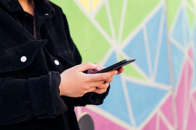 화려한 벽에 휴대폰으로 타이핑하는 알아볼 수 없는 젊은 여성의 손을 클로즈업