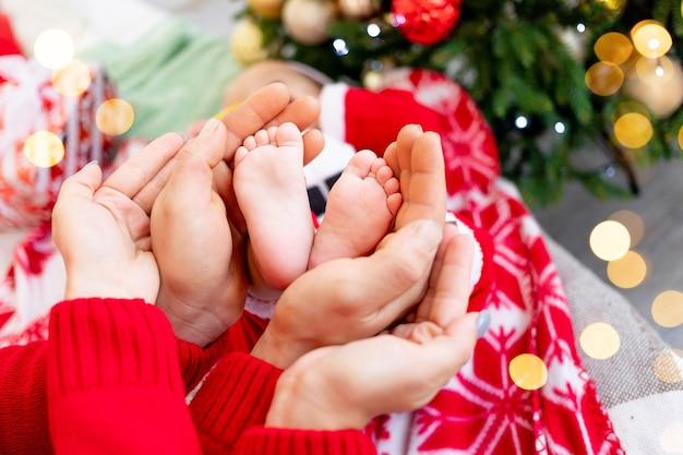 빨간 하트 모양의 장식, 새해와 크리스마스의 개념, 행복한 젊은 가족이 있는 크리스마스 트리에서 아기의 발을 잡고 있는 엄마와 아빠의 부모의 손 클로즈업