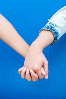 Закройте руки молодой пары, влюбленной в синюю стену