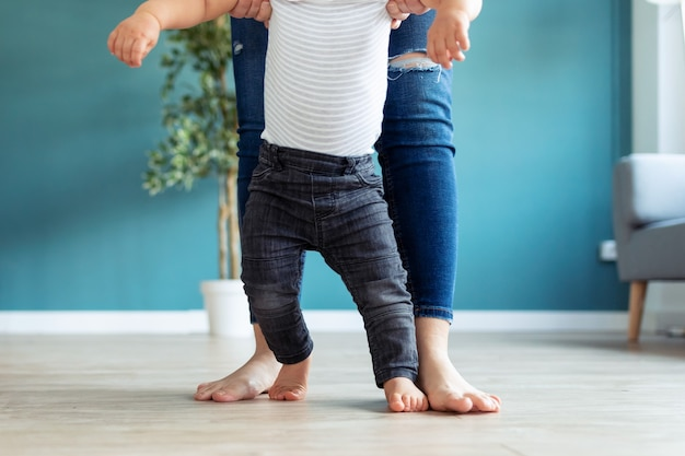 집에서 첫 걸음을 내딛는 데 도움이 되는 아버지와 아기 아들의 다리 클로즈업.