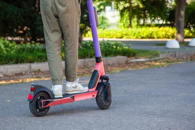 都市公園のアスファルトを背景に電子スクーターで若い男の足のクローズアップ