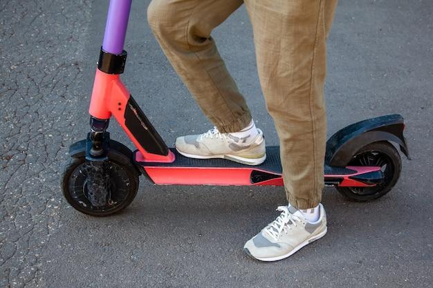 アスファルトを背景にした電子スクーターの若い男の足のクローズアップ。キックスクーターの共有