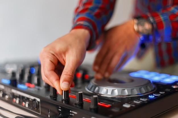 남성 dj 손의 클로즈업이 오디오 믹싱 콘솔에서 재생됩니다.