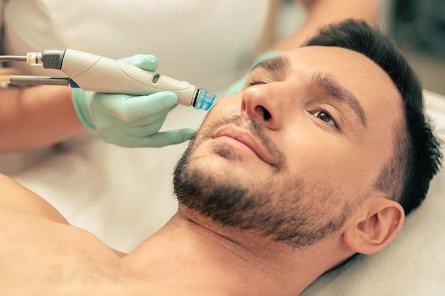 Мужчина выглядит спокойным и держит руку в резиновой перчатке с современным инструментом рядом с его лицом во время процедуры по питанию кожи