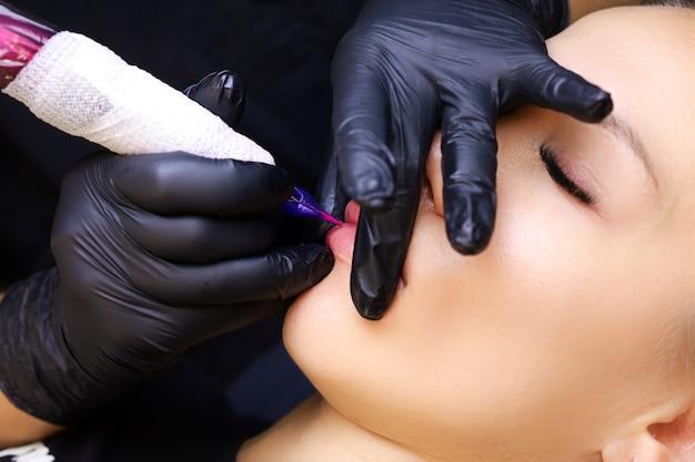 マスターのクローズアップは唇の下部をタトゥーで埋めます