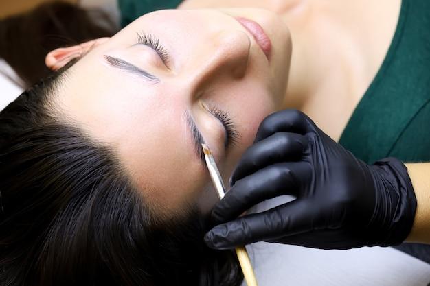Крупный план рук мастера, наносящих ламинирующие составы на брови модели кистью.