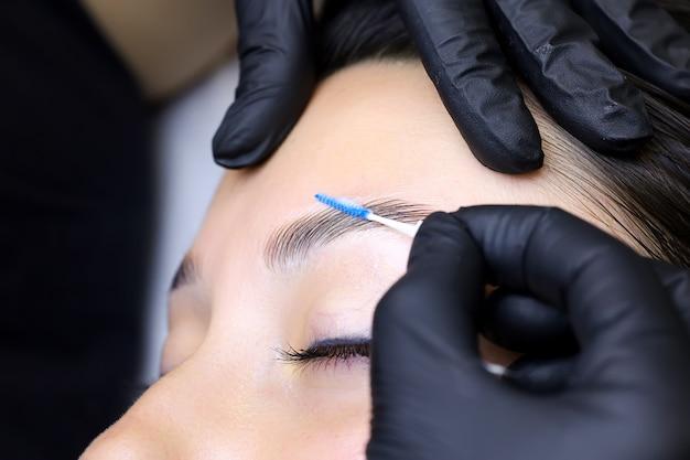 Крупный план рук мастера, держащего микрочистку, расчесывающую брови, и модели после процедуры ламинирования бровей.