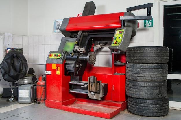 Крупный план современного шиномонтажного станка для ремонта и ремонта литых дисков на фоне мастерской по ремонту автомобилей и шиномонтажу