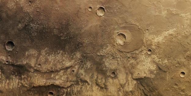 表面にクレーターと断層がある黄色の月の表面のクローズアップ