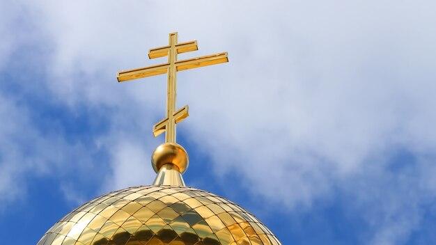 Крупным планом православный золотой крест на крыше