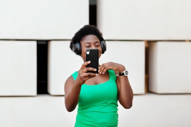 携帯電話のワイヤレス ヘッドフォンで音楽を聴き、踊り、自撮りをするアフリカの女の子が手に取った携帯電話の接写。