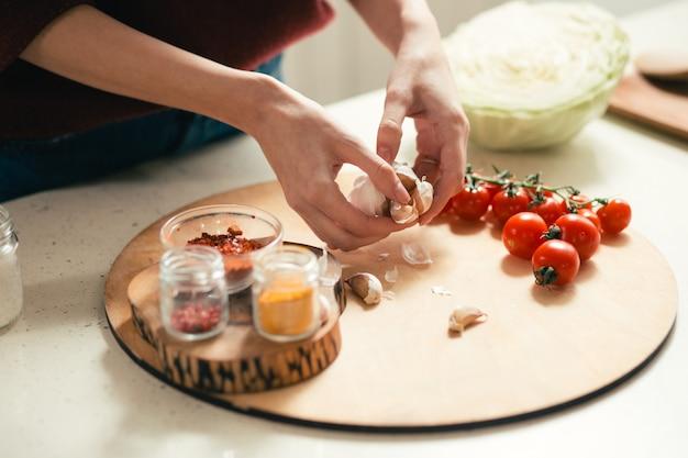 まな板とチェリートマトの上にニンニクを持っている女性の手でテーブルのクローズアップ