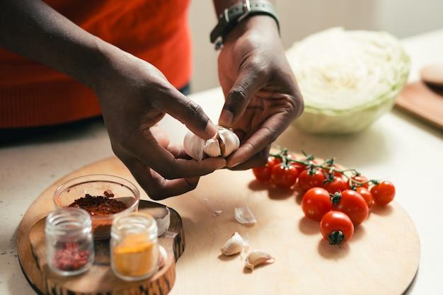 まな板とニンニクを持っている人の手に野菜とスパイスでテーブルのクローズアップ