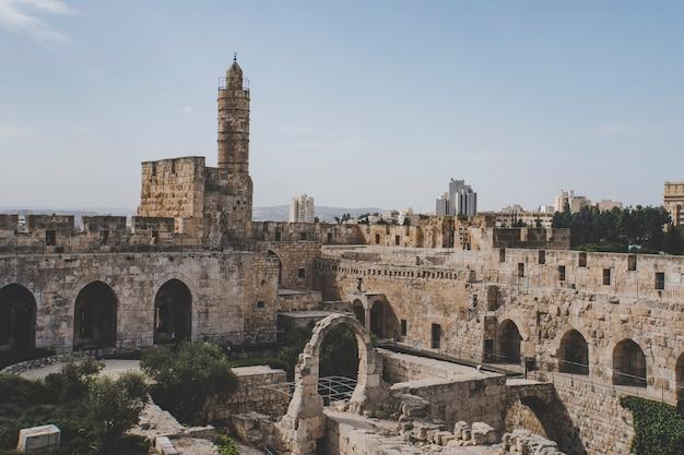 맑은 하늘을 배경으로 다윗의 탑과 예루살렘의 오래된 성벽을 닫습니다. 예루살렘의 구시가지 입구에 있는 고대 유대인 성채. 예루살렘, 이스라엘.