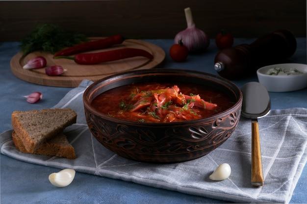 Крупный план традиционного русского борща из капусты, свеклы и других овощей, который подается на глиняной керамической тарелке со сметаной и чесноком. концепция национальной кухни. выборочный фокус.