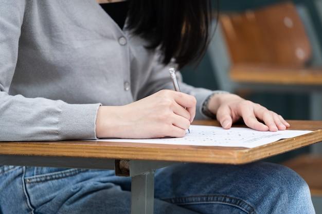 강의를 듣고 공부하는 동안 교실에서 공책에 메모를 작성하는 대학생의 클로즈업. 나무 데스크탑에 있는 메모장에 쓰는 여성의 손 클로즈업