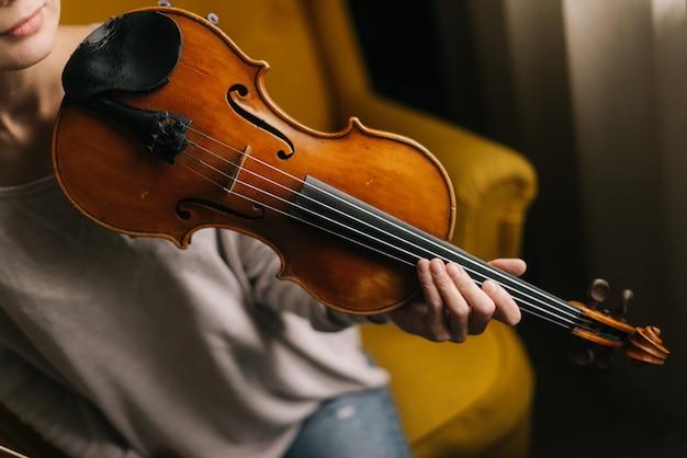 Крупный план скрипки на плече девушки. красивая молодая женщина позирует со скрипкой, сидя на мягком стуле в комнате с современным интерьером. музыкант девушка позирует с музыкальным инструментом