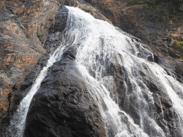 Крупный план движения водопада в парке. струя воды обтекает скалу и падает