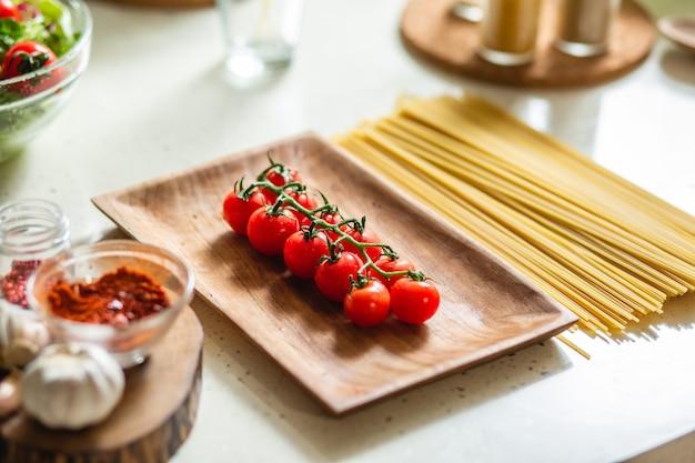 近くのテーブルに置かれたチェリートマトとスパゲッティの枝と木の板のクローズアップ