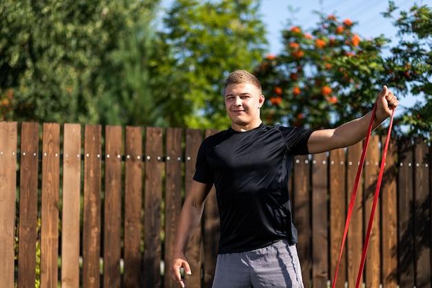 若い男のクローズアップは、夏の日に裏庭で自宅でスポーツに行きます。スポーツゴムで運動をしている若いスポーツマン
