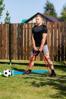 若い男のクローズアップは、夏の日に裏庭で自宅でスポーツに行きます。マットの上にスポーツゴムでスクワットをしている若いスポーツマン