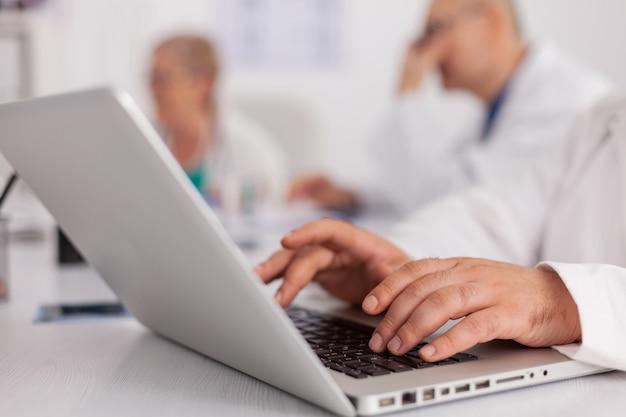 치료사 의사의 클로즈업은 랩톱 컴퓨터에서 알약 약물 치료 타이핑 질병 전문 지식을 처방합니다. 질병 진단을 분석하는 회의실에서 책상에 앉아 있는 개업의 남자