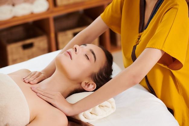 그녀가 눈을 감고 침대에 누워 있는 동안 젊은 여성에게 마사지를 하는 치료사의 클로즈업