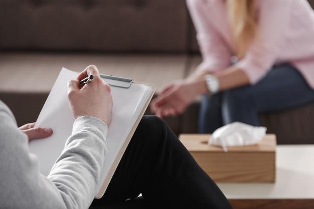 흐릿한 배경에서 소파에 앉아 있는 한 여성과 상담하는 동안 치료사가 손으로 메모를 작성하는 클로즈업.