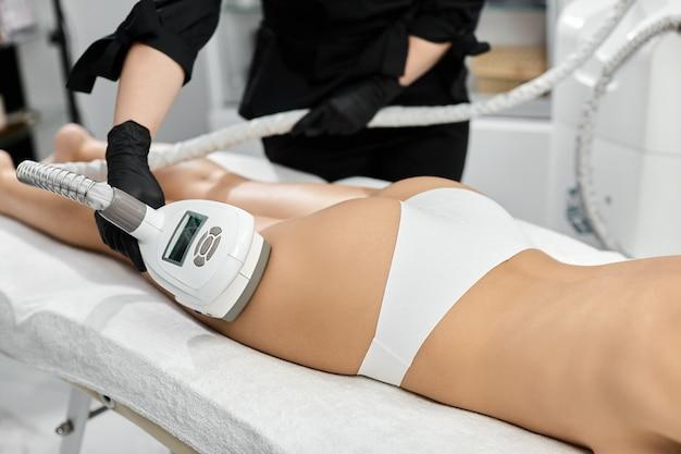 Крупный план терапевта, массирующего женскую ногу с помощью массажера lpg