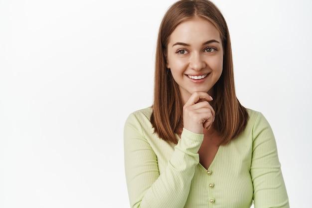思いやりのある若い成功した女性のクローズアップ、満足して笑って、脇を見て、プロモーションテキストを読んで、満足しているロゴを見て、考えて、白い壁の上に立っています。