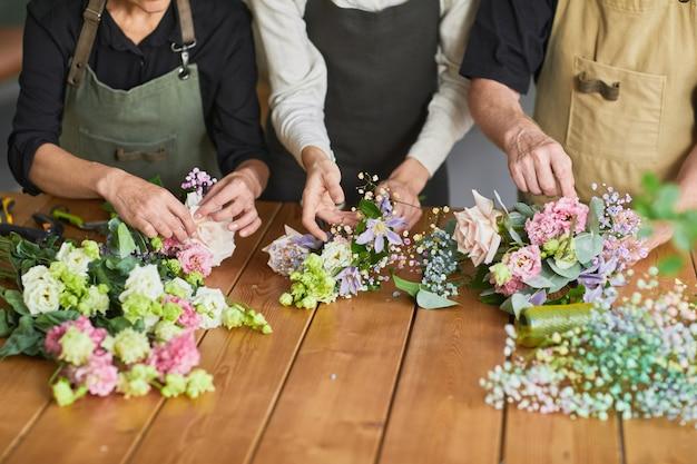 Крупным планом трех флористов, устраивающих цветочные композиции на деревянном столе в уютной мастерской копии пространства