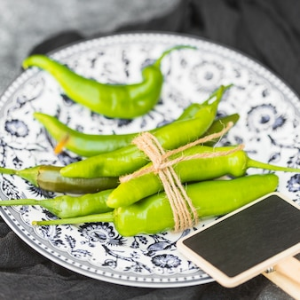 Close-up of tied fresh green chili peppers and blank slate on plate