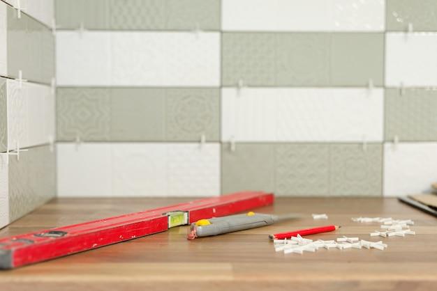 Крупный план укладки плитки, плитки приклеенной на цемент, приспособление уровня для ровных швов, никто