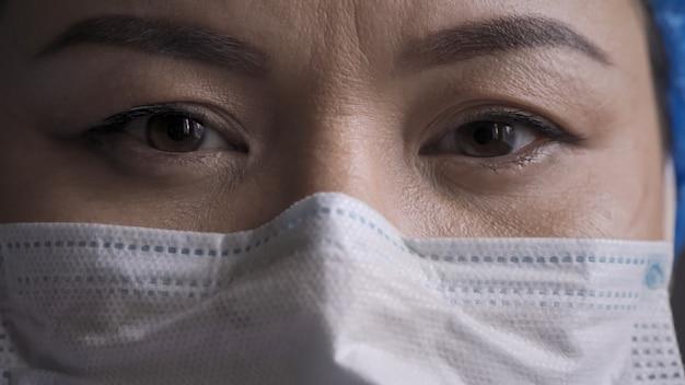 疲れた医師の目のクローズアップ。カメラを見て防護マスクを着ている女性。メディックは長時間残業の後でストレスを感じる