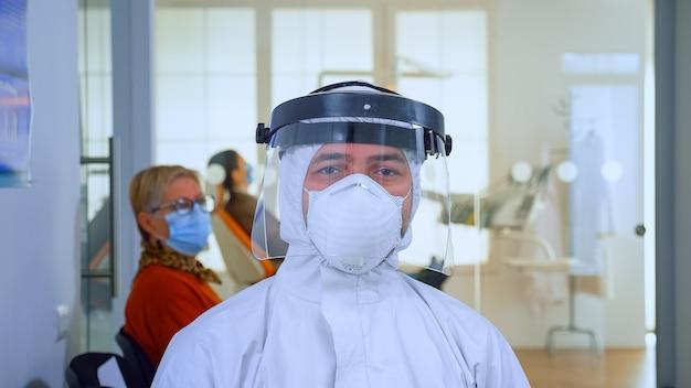 全体的に身に着けているカメラと待合室クリニックの椅子に座っているフェイスシールドを見ている口腔病学オフィスの疲れた医者のクローズアップ。コロナウイルスの発生における新しい通常の歯科医の訪問の概念