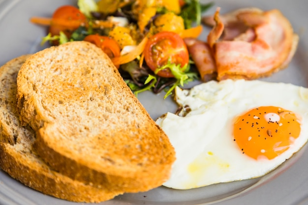 Крупный план тоста; жареные яйца; салат и бекон на серой керамической тарелке