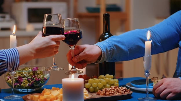 낭만적인 저녁 식사를 하는 동안 토스트와 부딪치는 레드 와인 잔을 닫습니다. 데이트에서 행복한 쾌활한 커플이 아늑한 주방에서 함께 식사를 하고, 식사를 즐기고, 기념일을 축하합니다.