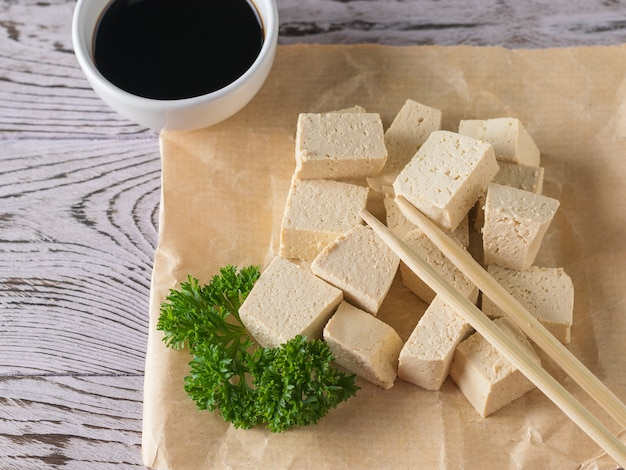 Крупным планом сыр тофу с соевым соусом и палочками для еды. соевый сыр. вегетарианский продукт.