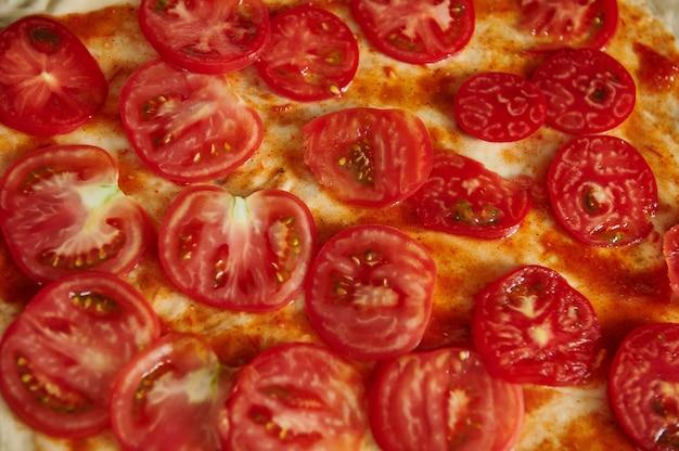 ピザ生地のトマトスライスのクローズアップ。フラットレイ、上面図、パターン。ハイアングルビュー