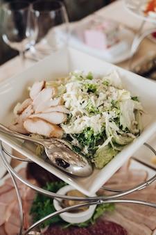 レタスとチキンの伝統的なシーザーサラダのクローズアップは、宴会でサービングスプーンと正方形のプレートで提供されます。