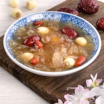 はすの実、赤いナツメ(ナツメ)、クコの実(ゴジベリー、ゴジベリー)を背景にした伝統的な中国の甘い雪のように白いシロキクラゲのスープのクローズアップ。